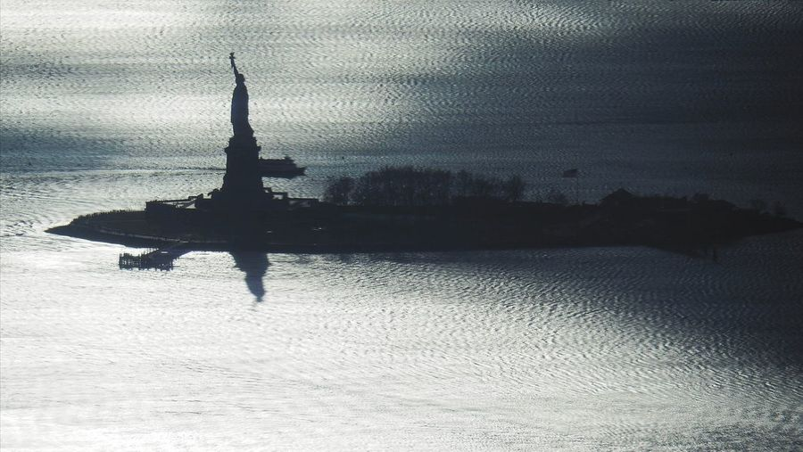 Silhouette of building on sea