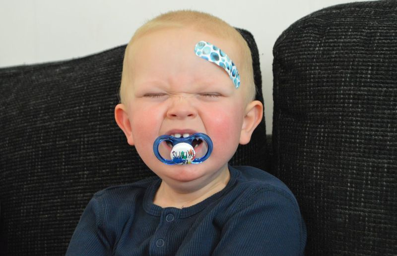 Close-Up Cute Boy With Pacifier In Mouth Crying At Home