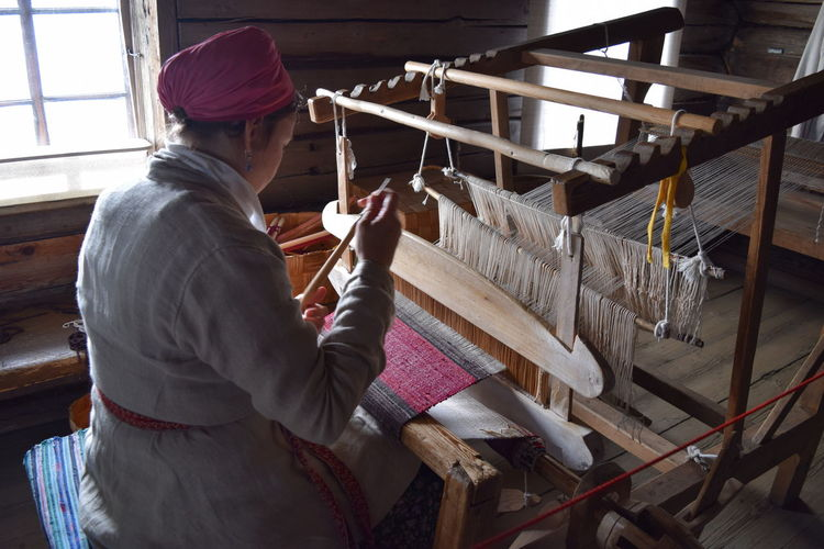 Adult Woman Working Workshop Business Clothing Concentration Factory Historical Holding Indoors  Industry Loom Occupation One Person Real People Side View Skill  Technology Textile Thread Waist Up Warm Clothing Weaving Working