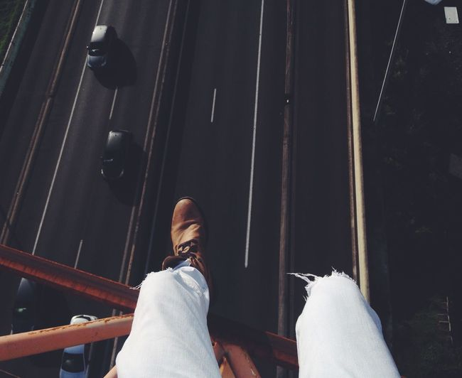 Low section of man sitting on bridge over road
