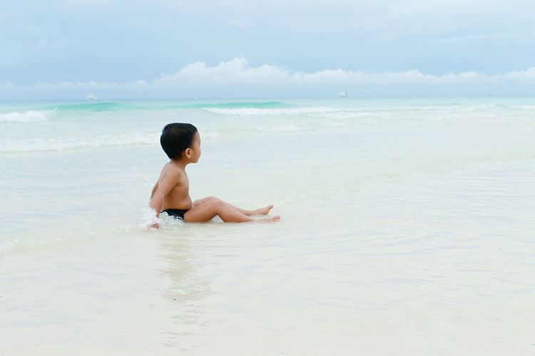 Travel Alone Journey Adventure Child Childhood Beach Sea Shirtless Vacations Summer Enjoyment Fun Sitting One Person Water Side View Carefree Leisure Activity Lifestyles Tranquility Relaxation One Man Only EyeEm Ready   An Eye For Travel