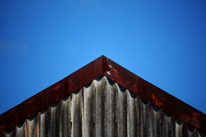 Low angle view of rusty metallic structure against blue sky