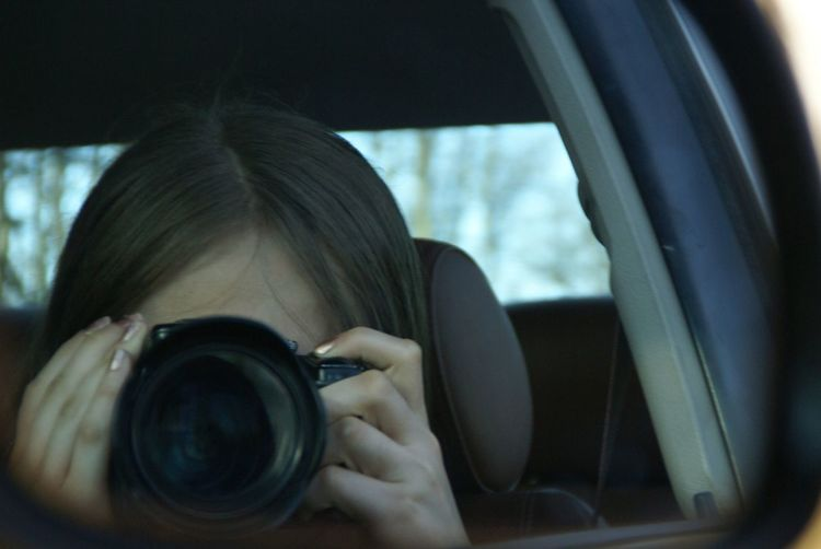 Reflection of girl photographing with camera on side-view mirror of car