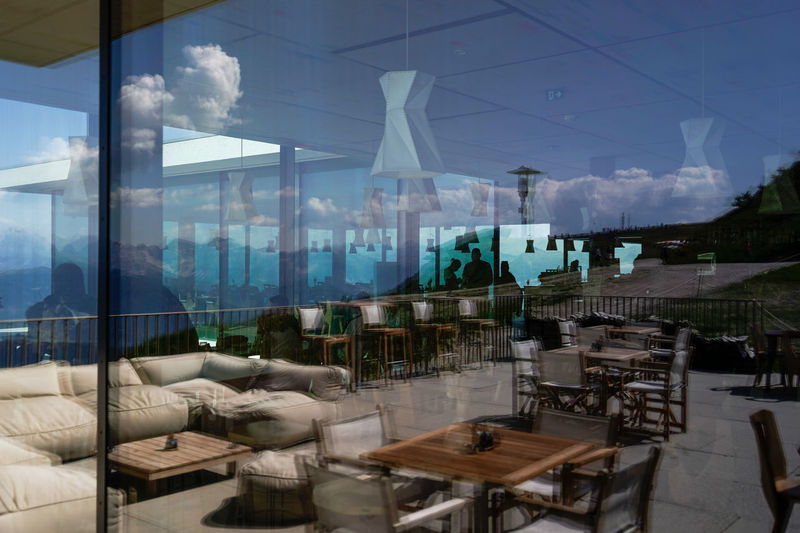 Chairs and tables in restaurant against sky seen through glass window