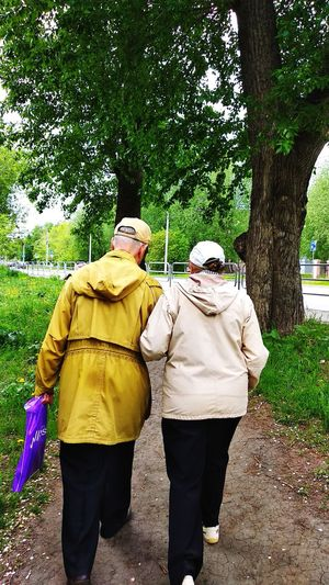Rear view of man and woman walking on footpath
