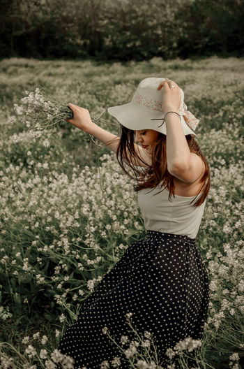 Side view of woman wearing hat standing amidst flowers