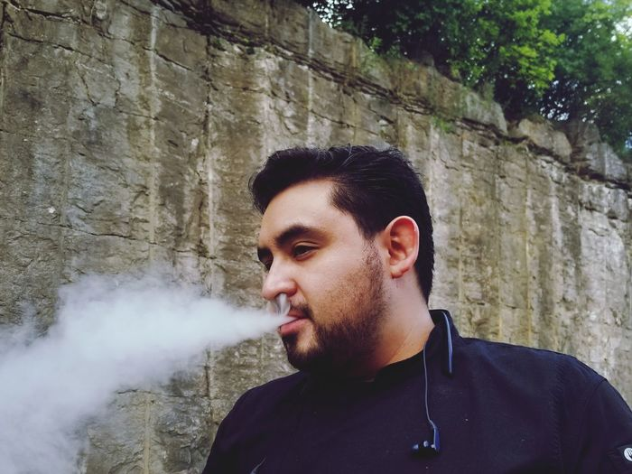 Man exhaling smoke while standing against wall