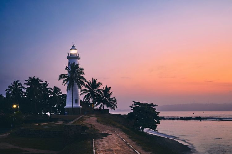 Lighthouse in fort in Galle. Old town in Sri Lanka at colorful sunrise. Galle Sri Lanka Lighthouse Guidance Direction Fort Safety Light Sunrise Moody Sky Sunset Palm Tree Architecture Tropical Climate Sea Nature Travel Destinations Travel Building Exterior Scenics - Nature Town City Landmark Costline Navigation