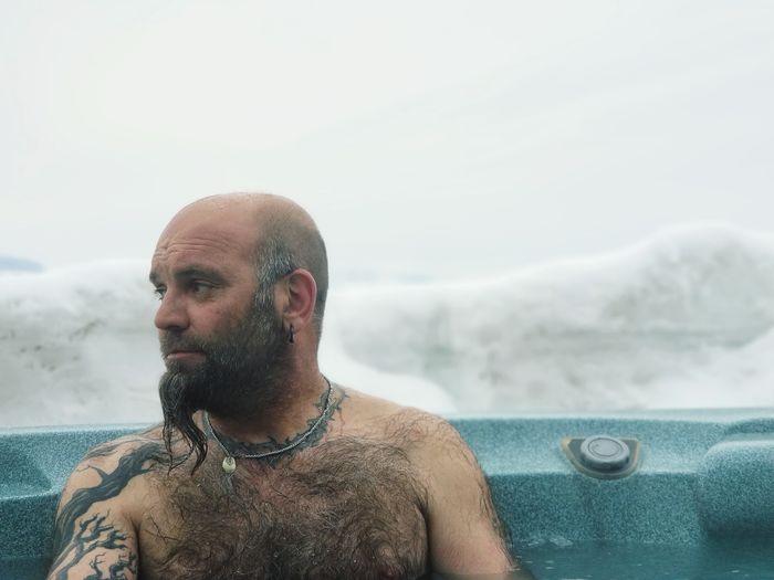 Shirtless man looking away in hot spring