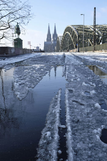 View of frozen river by buildings in city