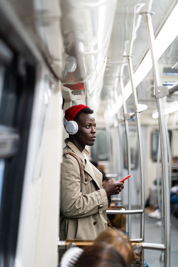 Young man listening music while standing in train