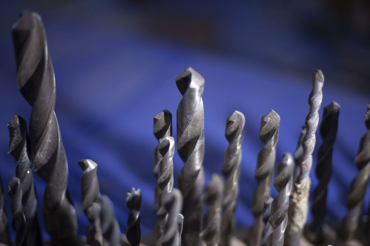 Close-up of metal hanging against blue sky