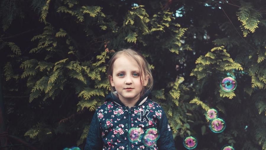 Portrait of cute girl against trees