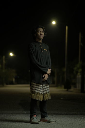 Young man looking away while standing on street at night