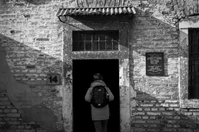 The entrance of one of the many sheds in Terezin. Shed number 14. 14 Architecture B&w Blackandwhite Boy Brick Wall Building Building Exterior Check This Out Cold Concentrationcamp Day Door Entrance House Light And Shadow Man Minimalism Photo Terezín Wall