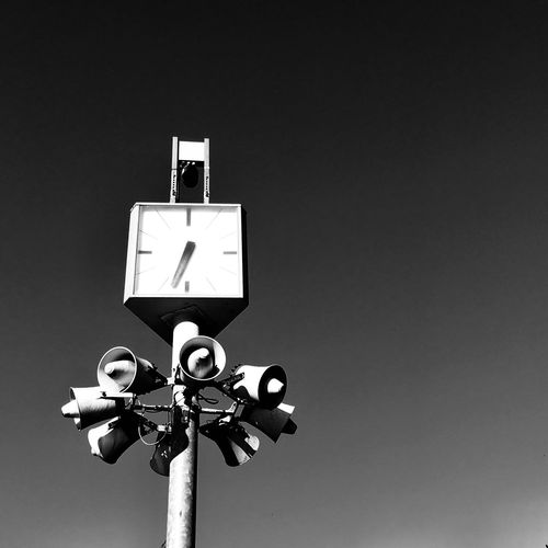 Low angle view of clock with megaphones on pole against clear sky