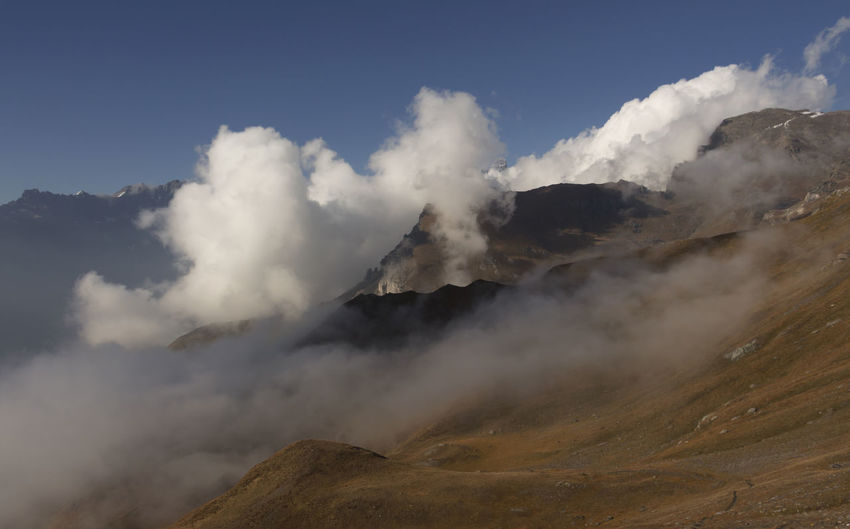 Scenic view of mountain peak surrounded by clouds