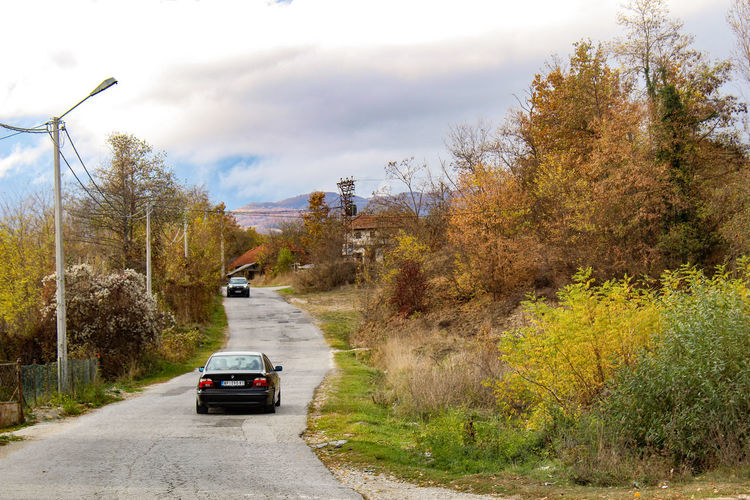 Cars on road against sky during autumn