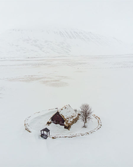 High angle view of snow covered land and turf church
