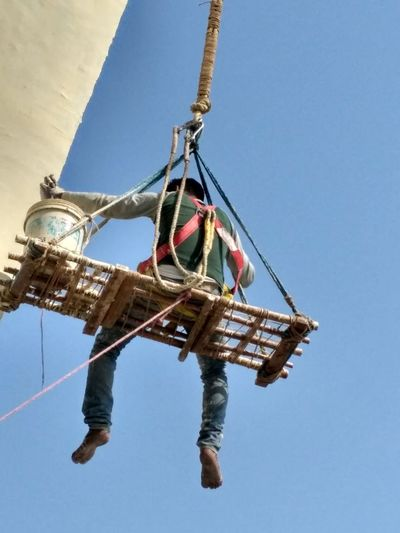 Low section of man holding rope against clear blue sky