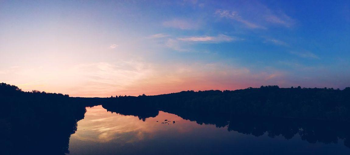 Scenic shot of calm lake at sunset