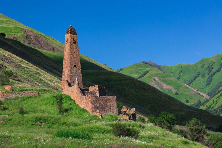 Built structure on landscape against clear blue sky
