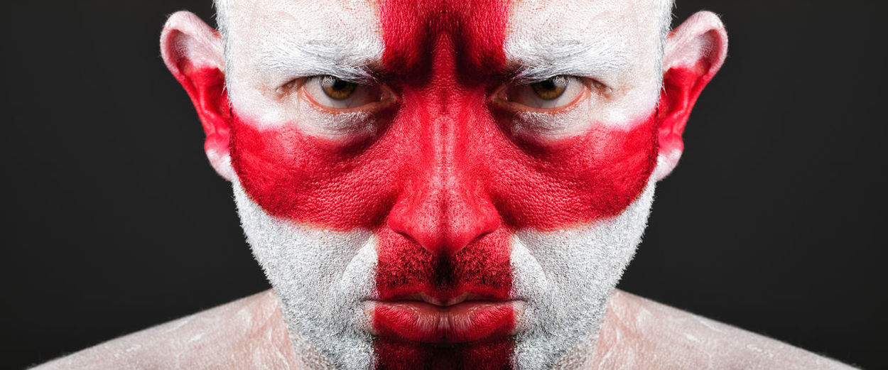 Close-up portrait of serious man with english flag body paint against black background