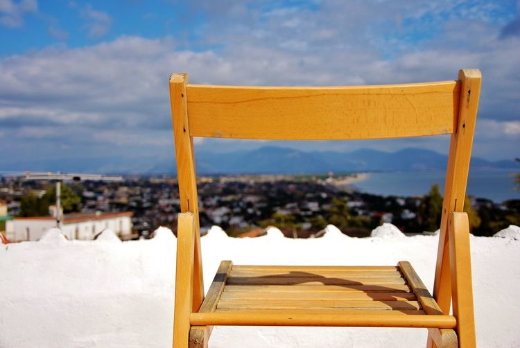 Chair on snow covered land against sky