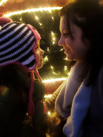 Young woman with hands on illuminated christmas tree during winter