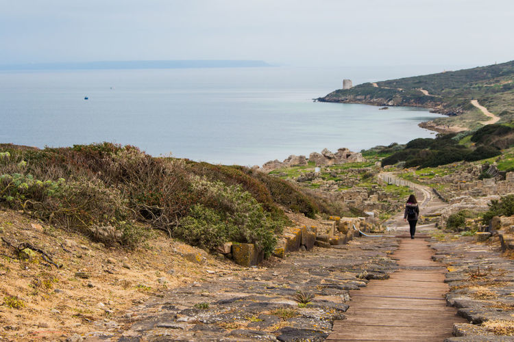 Woman walking on footpath against sea