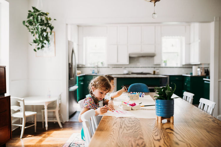 Rear view of girl on table at home