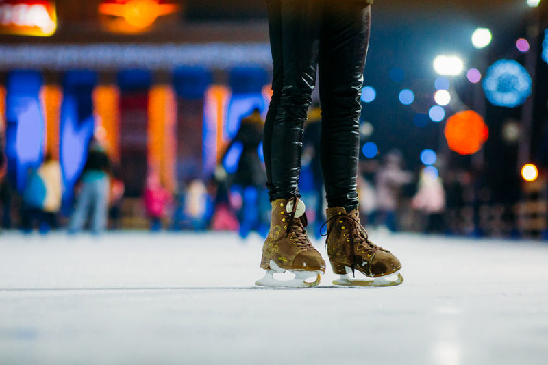 Low section of person ice-skating at night