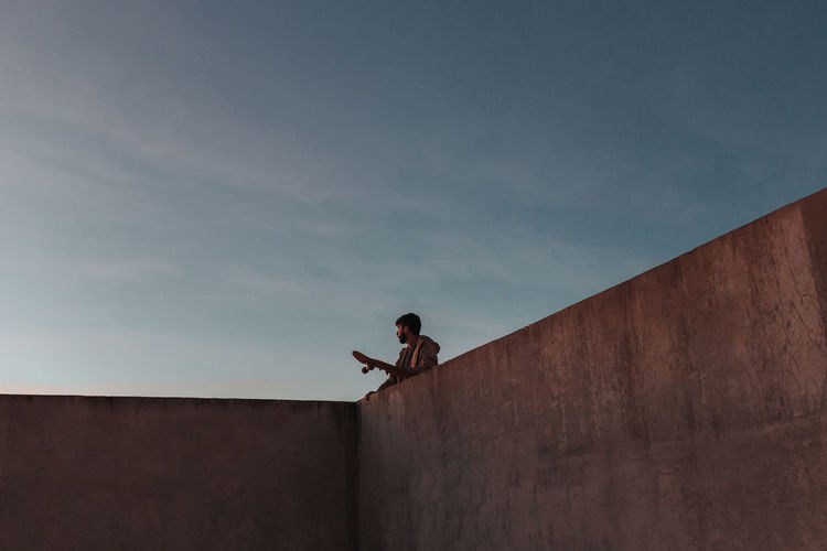 Low angle view of man standing on wall against sky