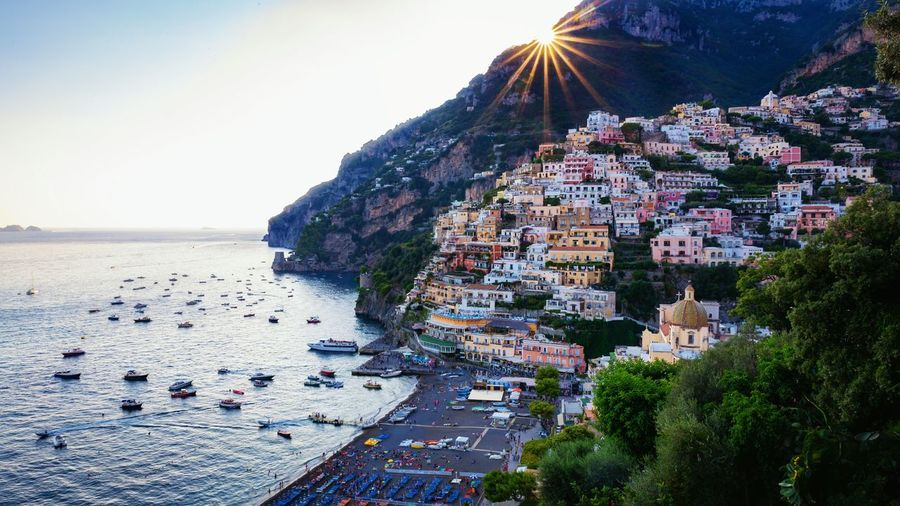 Positano Famous Places In Italy Travel Destinations Seaside Sunburst Positano EyeEm Selects Italy Costiera Amalfitana Bella Italia Amalfi Coast EyeEm Gallery Holidays Village Water Sea City Mountain Beach Sunset Summer Multi Colored Sky Sun Seascape 2018 In One Photograph Springtime Decadence