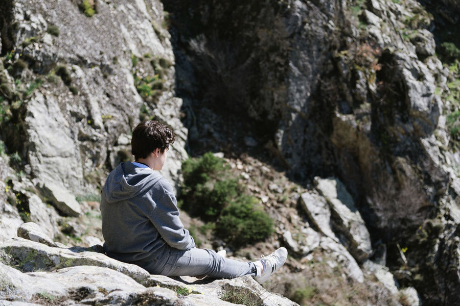 Young adult sitting on a rock looking at waterfall Adult Adventure Beauty In Nature Day Full Length Mountain Mountain Range Mountains Nature One Man Only One Person One Young Man Only Only Men Outdoors People Real People Relaxing Rock Rock - Object Rock Climbing Rock Formation Sitting Waterfall Waterfalls Young Adult