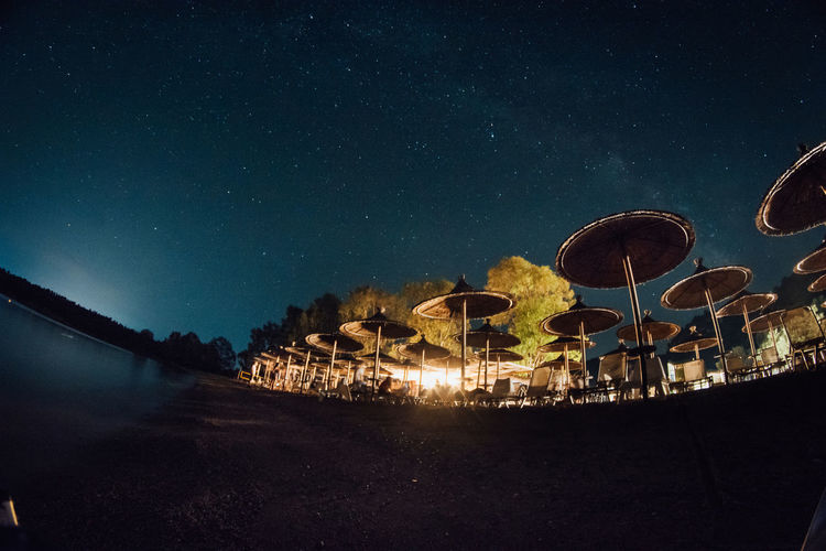 Low angle fish-eye lens shot of parasols against sky at night