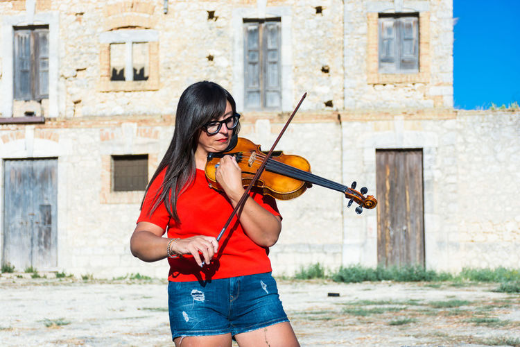 Woman playing violin while standing against building