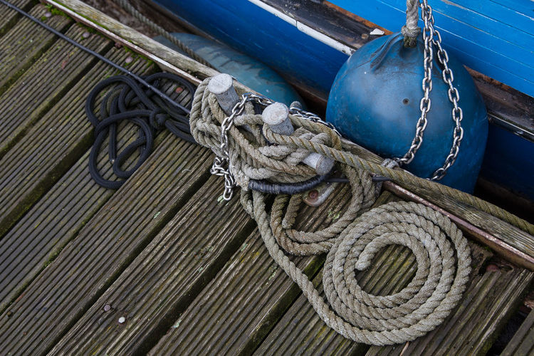 High angle view of rope tied to boat moored at harbor