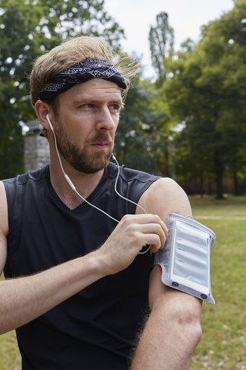 Man listening music while exercising against trees in park