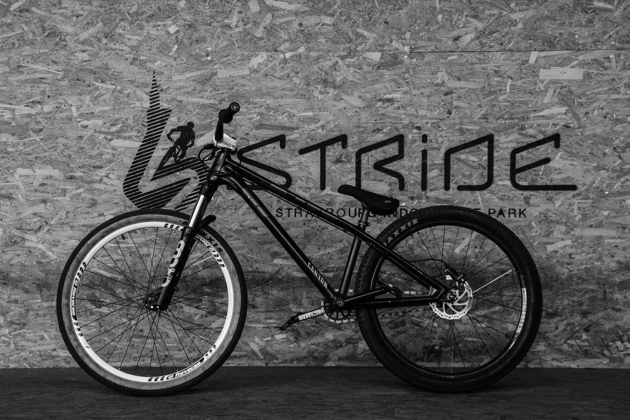 bicycle, transportation, land vehicle, mode of transportation, stationary, no people, day, text, western script, wall - building feature, wall, communication, outdoors, wheel, travel, high angle view, water, parking, protection