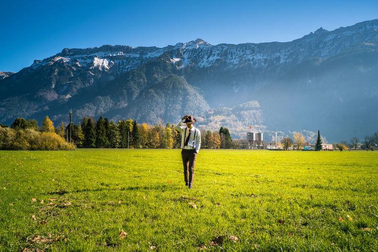 Full length of man walking on grassy field against clear sky