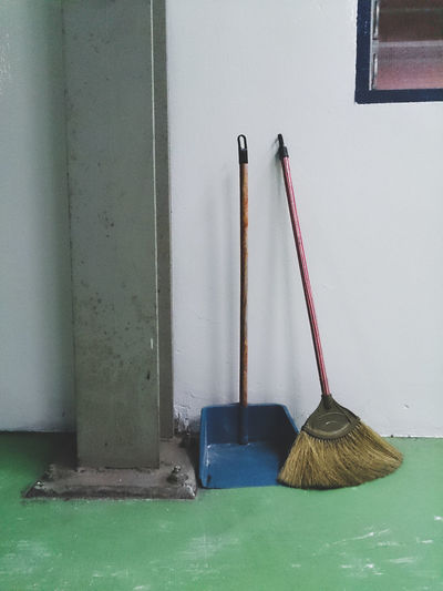 Broom with dust pan by wall