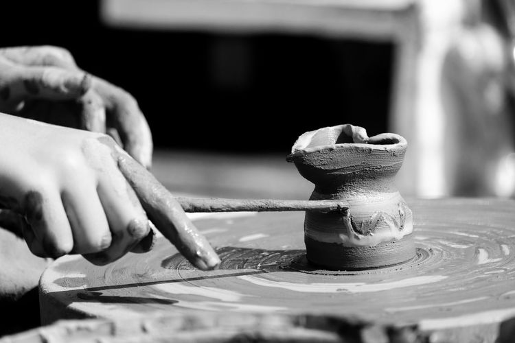 Cropped hand of person working on pottery wheel