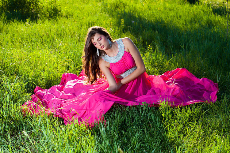 Beautiful young woman in an airy dress sitting on green grass Grass Plant One Person Field Land Green Color Real People Full Length Lifestyles Dress Clothing Young Women Women Beautiful Woman Young Adult Leisure Activity Fashion Nature Day Hairstyle Pink Color Outdoors Contemplation