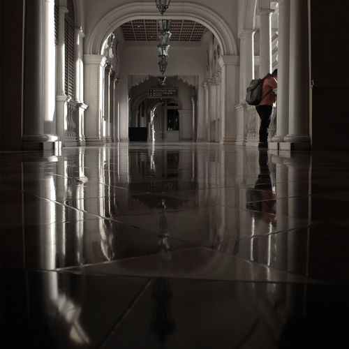 Reflection of woman standing in corridor of building