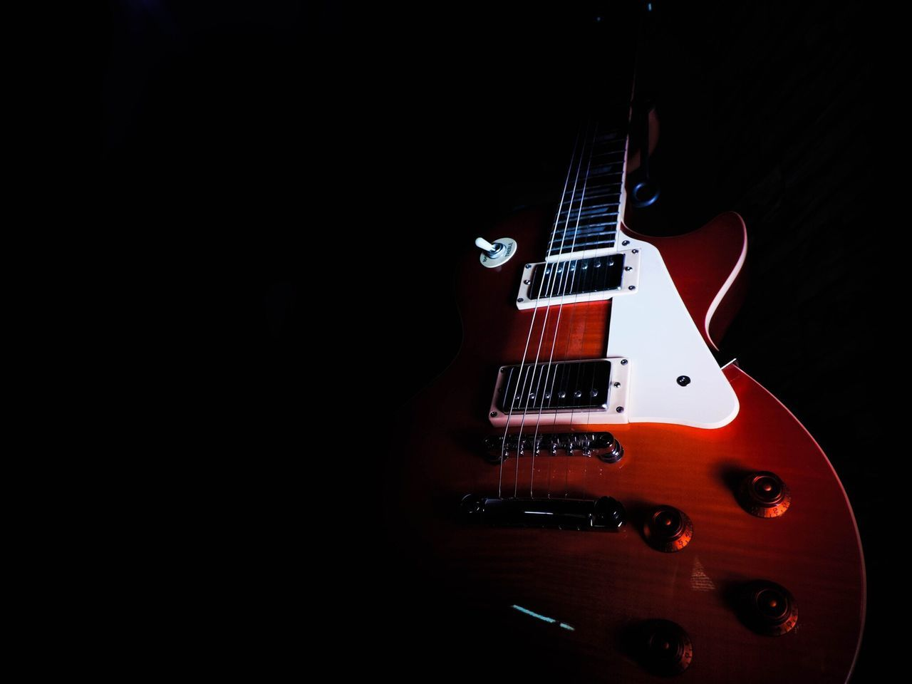 Close-Up Of Electric Guitar Against Black Background