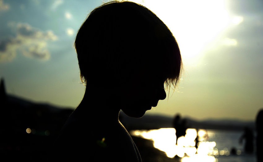 Close-up silhouette of girl at beach during sunset