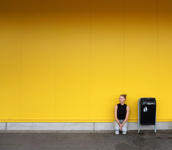 Woman Crouching Against Yellow Wall