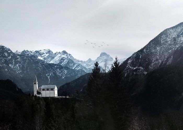 Distant view of historic church on mountain against sky during winter