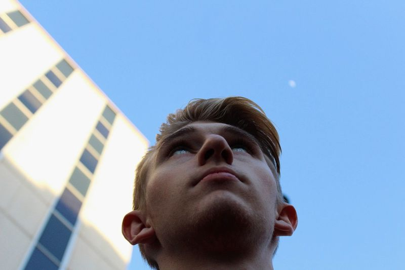 Low angle view of thoughtful young man against clear blue sky